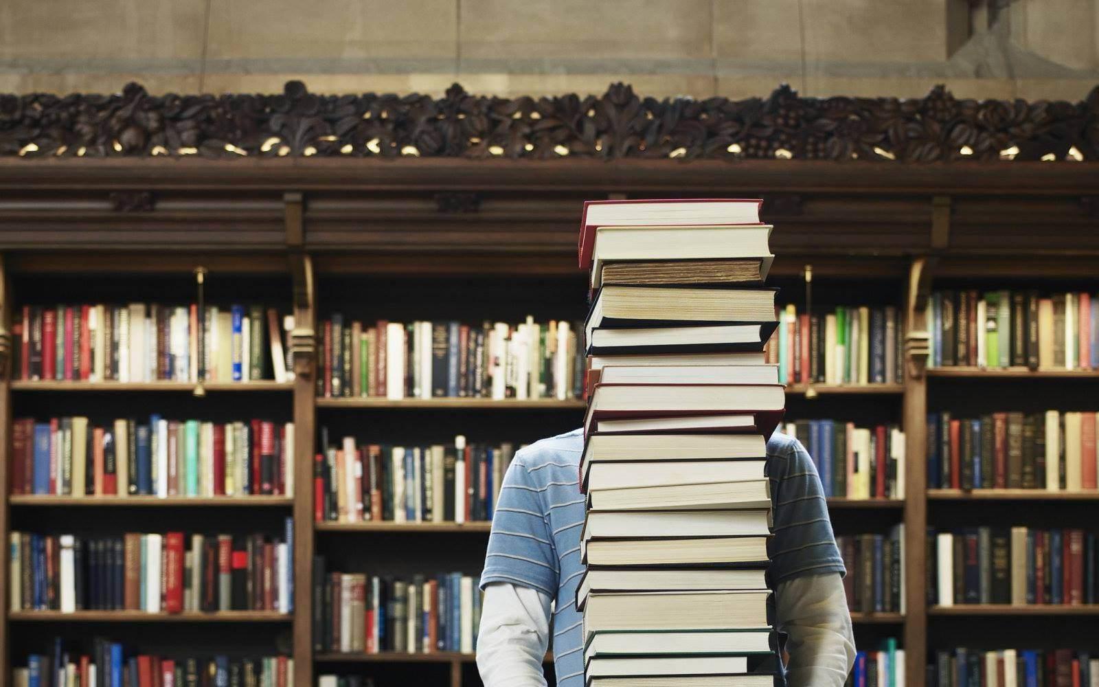 парень несет стопку книг