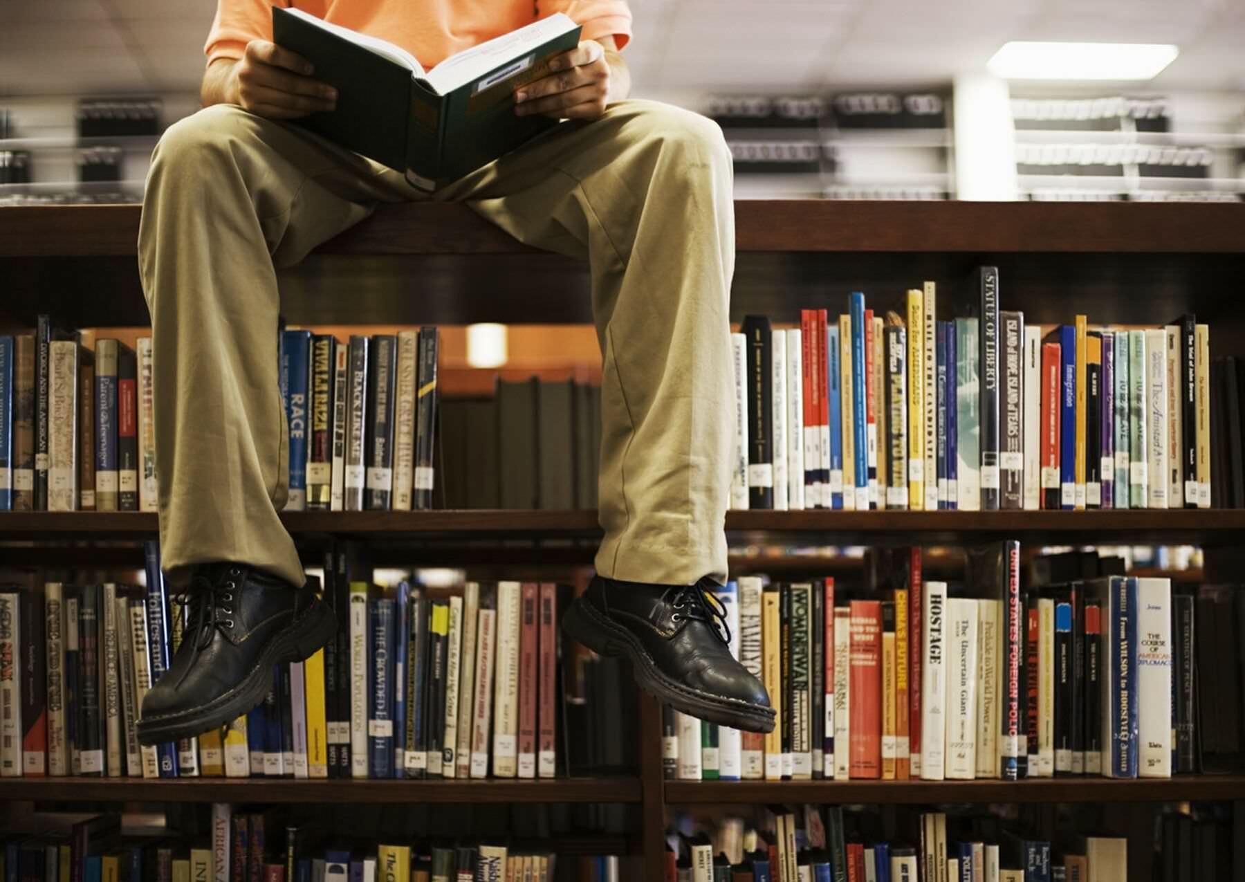 Читает на стелаже с книгами